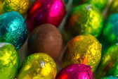 Colourful easter eggs with one unwrapped — Stock Photo