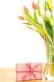 Florero de tulipanes en mesa de madera con regalo — Foto de Stock
