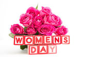 Bouquet of pink roses next to wooden blocks spelling womens day — Stock Photo