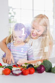 Mother and daughter chopping vegetables with holographic interfa — Stock Photo