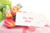 Bouquet of tulips next to a gift with a card for a mother — Stock Photo