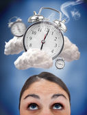 Woman looking up at ringing alarm clocks in clouds — Stock Photo