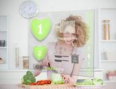 Smiling woman making salad using hologram interface — Stock Photo