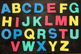 Alphabet magnets stuck on blackboard — Stock Photo