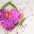 Light shining over heart made of pink confetti framed by tulips - Foto Stock