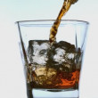 Stock Video: Whiskey pouring into tumbler with ice