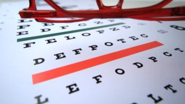 Red reading glasses falling onto eye test close up — Stock Video