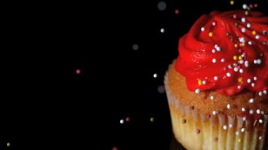 Colourful sprinkles pouring onto cupcake on black surface — Stock Video