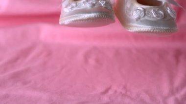 Baby booties falling on pink blanket — Stock Video