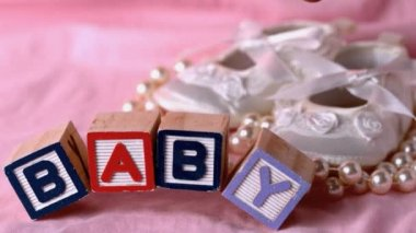 Baby in letter blocks beside booties and pearls on pink blanket — Stock Video