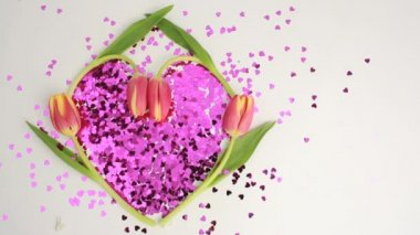 Light shining over heart made of pink confetti framed by tulips — Stok video