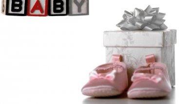 Blocks spelling baby falling beside booties and gift box — Stock Video