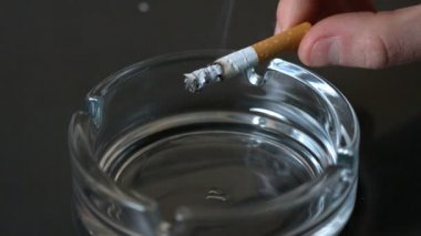 Hand tipping ash from cigarette into ashtray — 图库视频影像