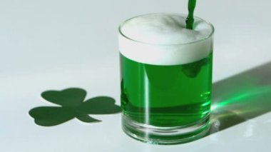 Green beer pouring into a tumbler beside paper shamrock in slow motion — Stock Video