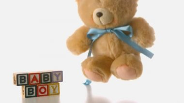 Fluffy teddy bear falling besides baby blocks — Stock Video