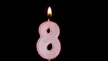 Eight birthday candle flickering and extinguishing on black background — Stock Video