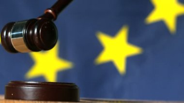 Gavel falling onto sounding block with european union flag in background — Stock Video