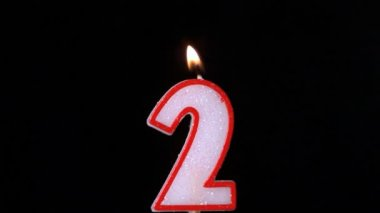 Two birthday candle flickering and extinguishing on black background — Stock Video