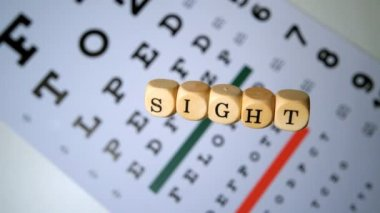 Dice spelling out sight falling onto eye test beside glasses — Vídeo Stock