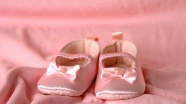 Pink booties falling on pink blanket — Stock Video