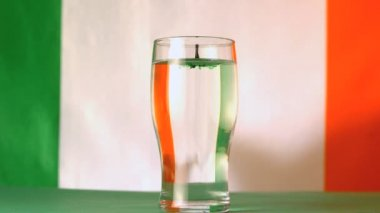 Irish flag mirrored through pint of water with green drop falling in in slow motion — Stock Video