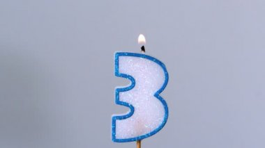 Three birthday candle flickering and extinguishing on blue background — Stock Video