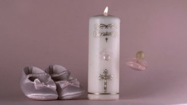 Baby shoes falling beside lit baptism candle and pink pacifier — Stock Video