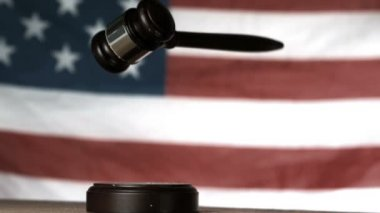 Gavel dropping onto sounding block with american flag in background — Stock Video