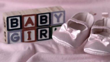 Baby booties falling on pink blanket with baby girl message in blocks — Stock Video