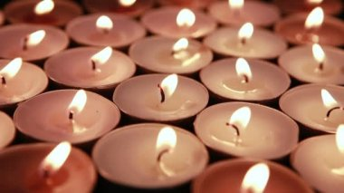 Wind blowing out many tea light candles — Stock Video