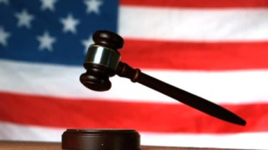 Gavel dropping on sounding block with american flag in background — Stock Video