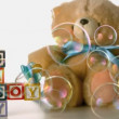 Bubbles floating over baby blocks, soother and teddy bear — Stock Video #25630195