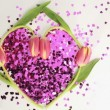 Heart made of pink confetti framed by tulips dispersing — Stock Video