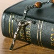 Rosary beads falling onto bible on table — Stok Video #25630793