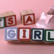 Its a girl message in letter blocks beside pink booties — Stock Video