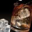 Ice cubes falling into tumbler of whiskey and ice — Stock Video