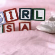 Its a girl message in letter blocks beside booties on pink blanket — Stockvideo