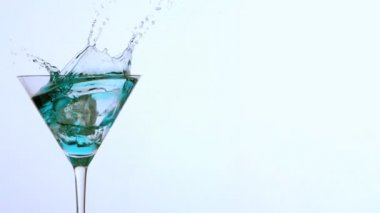 Ice falling into cocktail glass of blue alcohol on white background — Stock Video