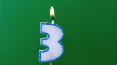Three birthday candle flickering and extinguishing on green background — Stock Video