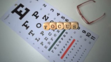 Dice spelling out focus falling onto eye test beside glasses — Stock Video