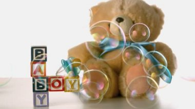 Bubbles floating over baby blocks, soother and teddy bear — Stock Video