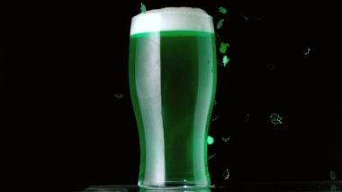 Shamrock confetti falling in front of pint of green beer — Stock Video