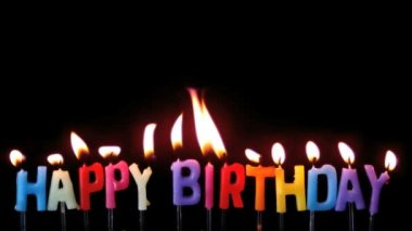 Colourful happy birthday candles being blown out with copy space on black background — Stock Video