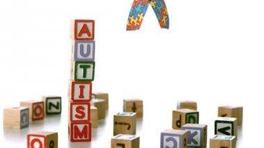 Autism ribbon falling beside blocks spelling autism — Stock Video