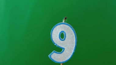 Nine birthday candle flickering and extinguishing on green background — Stock Video
