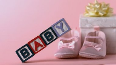 Baby blocks toppling over with booties and gift box in background — Stock Video