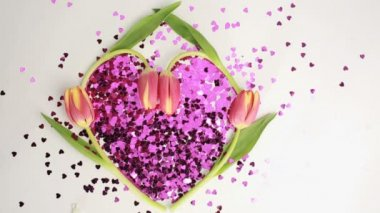 Heart made of pink confetti framed by tulips dispersing — Стоковое видео