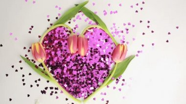 Heart made of pink confetti framed by tulips dispersing — Vidéo