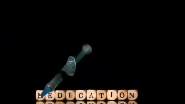 Syringe falling in front of dice spelling medication on black background — Stock Video