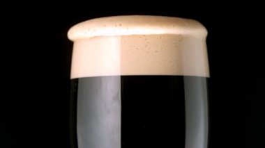 Foam head settling on pint of stout — Stock Video